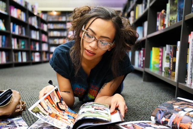 Girl-reading-a-graphic-novel-on-the-floor-of-a-bookstore-how-graphic-novels-help-my-writing-susan-shiney-benefits-of-reading-graphic-novels-joe-ciciarelli-unsplash